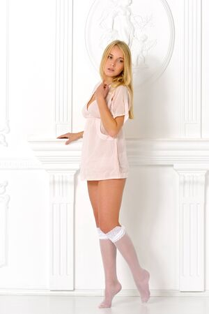 Beautiful blonde woman in studio with white antique background. She is dressed in white lingerie and stockings.
