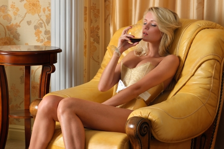 undressed: Beautiful woman in underwear with glasss o red wine in luxury interior.