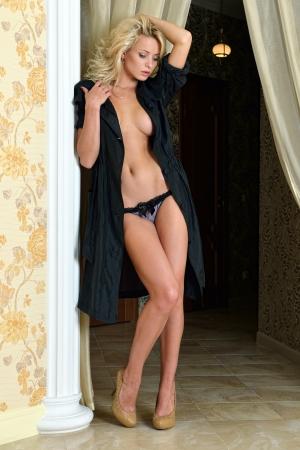 the naked girl: Hermosa mujer rubia en traje de seda negro en el interior de lujo.