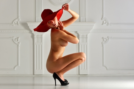 nude woman in a red hat in luxury interior. Stock Photo