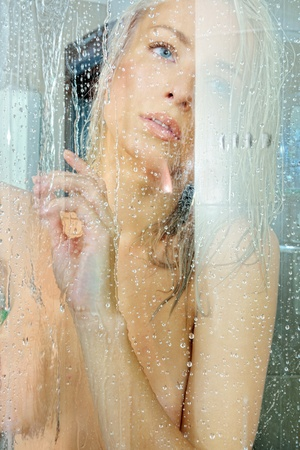 Beautiful blonde nude woman in a shower. Torso portrait. photo