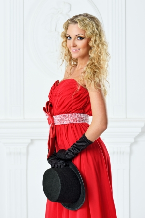 red evening: Beautiful woman in a red evening dress with mans hat.