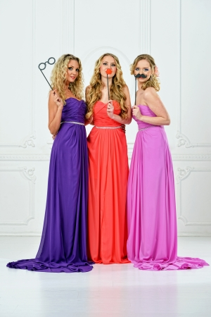 evening gown: Group of women in evening gown with masks. Stock Photo