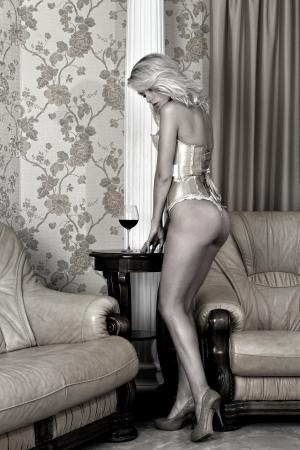 femme se deshabille: Belle femme en sous-v�tements dans l'int�rieur de luxe. Image monochrome.