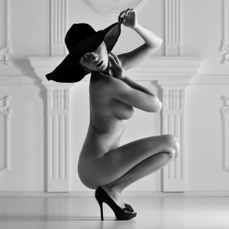 Nude woman in a red hat in luxury interior. Monochrome inage.