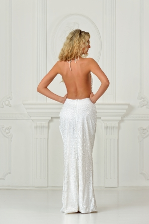 lux: Beautiful bonde woman in sexy white long dress with unclad back. Shooted in white interior studio. Stock Photo