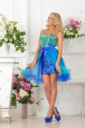 lux: Beautiful blonde woman in short blue gown dress. Studio with luxury interior with  flowers.