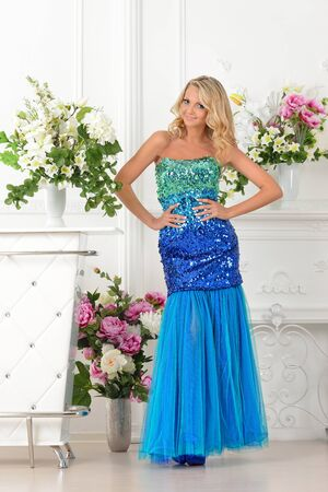 lux: Beautiful blonde woman in long blue gown dress. Studio with luxury interior with  flowers.