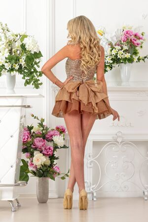 short back: Beautiful blonde woman in brown gown dress. Luxury studio with flowers.