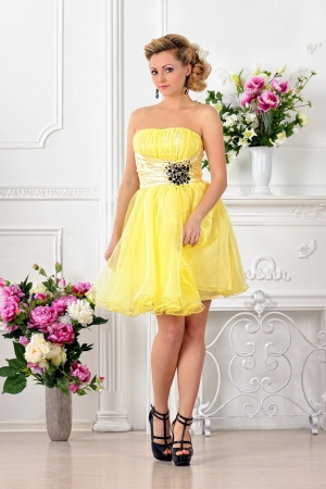 lux: Beautiful woman in yellow gown dress. White Luxury studio with flowers. Stock Photo