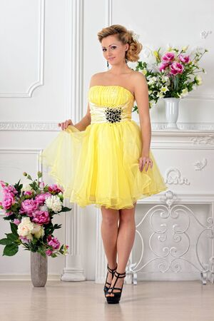 Beautiful woman in yellow gown dress. White Luxury studio with flowers. Stock Photo - 21139498