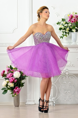 violaceous: Beautiful woman in violet gown dress  White Luxury studio with flowers  Stock Photo