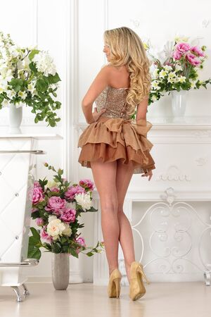 lux: Beautiful blonde woman in brown gown dress. Luxury studio with flowers.