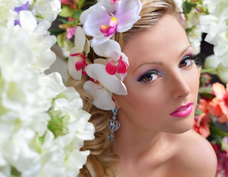 Portrait of the beautiful chic woman around the flowers.