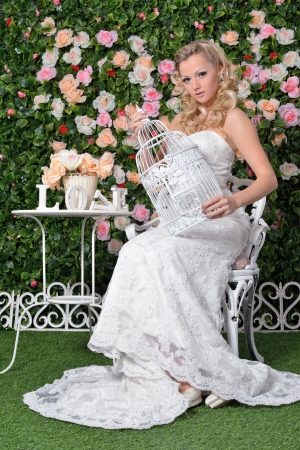 lux: Beautiful woman in wedding luxury dress. She is sitting in Garden with beautiful flowers. Stock Photo