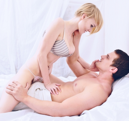 Beautiful naked couple is holding and kissing in the bedroom.