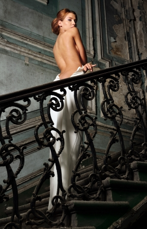 portrait of the beautiful woman in white dress with bared back. She is going upstairs. Studio with interior of old palace. Stock Photo - 22284031