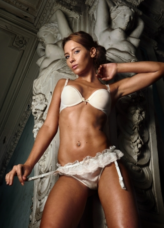 Portrait of the beautiful woman in white underwear. Studio with interior of old palace with marble statues.  photo