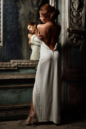 Portrait of the beautiful woman in white dress with naked back. She is standing at the mirror. Studio with interior of old palace. Not necessary property release. photo
