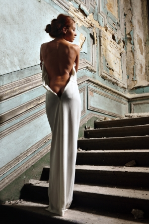 portrait of the beautiful woman in white dress with naked back. She is going upstairs. Studio with interior of old palace. Not necessary property release. photo