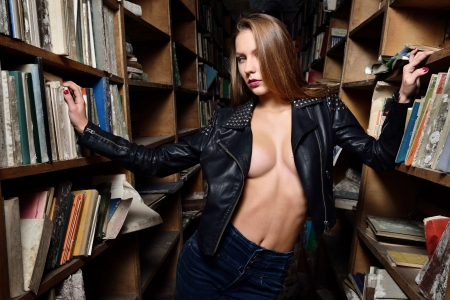 Beautiful sexy woman with naked torso. She is posing in the old library. photo