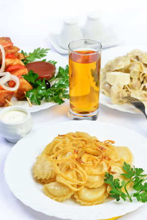 gass: White table with food of meat on skewer, dumplings and gass of juice. still life of setout table Russian cuisine