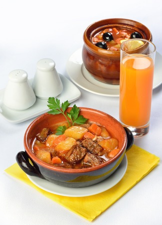 squeak: Still life of setout table with soup and meat in ceramic pots and juice. Image with white background. Russian cuisine Stock Photo