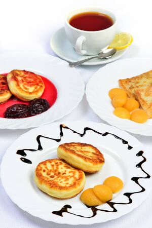 sause: White table with food  Crepes, cheesecakes with berry sause and cup of tee  still life of setout table  Russian cuisine