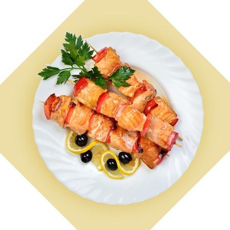 brochetas de frutas: Plato de salmón pescado en el pincho en la placa blanca Imagen aislada con blanco bckground Vista desde arriba bodegón de mesa replanteo cocina rusa Foto de archivo