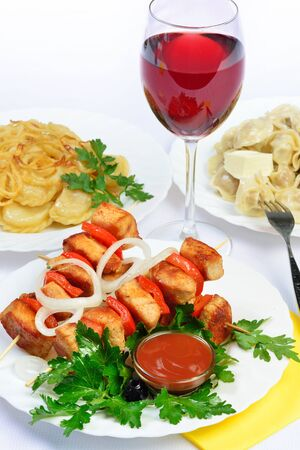gass: White table with food of meat on skewer, dumplings and gass of red wine. still life of setout table  Russian cuisine
