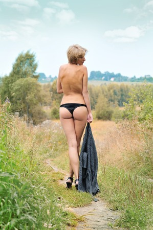 Back of the Beautiful naked woman walking at the meadow outdoors. photo