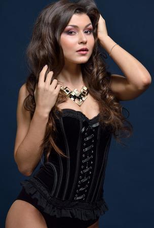 Beautifu femme en lingerie noire posant en studio.