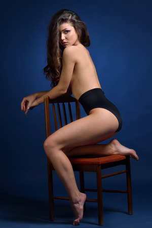 Beautiful naked woman in black panty sitting on the chair. Studio shooting. photo