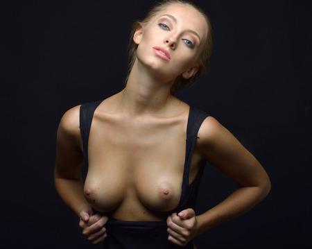 Beautiful blonde woman with naked breast in a black underwear posing in a dark Studio. Torso portrait. Stock Photo