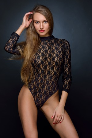 Beautifu woman with long hair in black lace lingerie, semi-dress posing in studio.