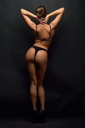 beautiful woman posing in black lingerie in studio. Back view.