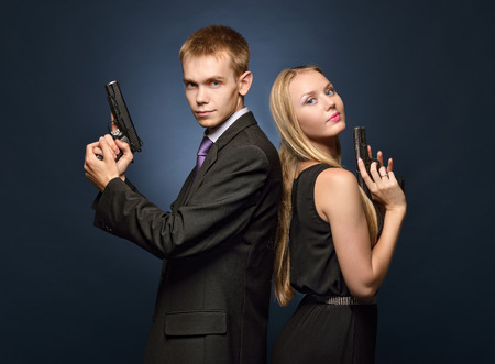 character assassination: beautiful couple in evening dresses  with a guns. Photoshooting in criminal and a spy style.