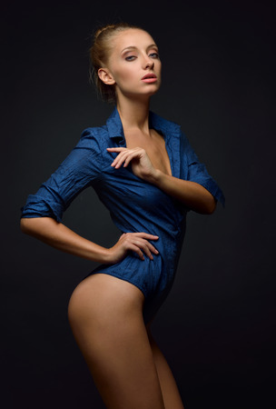 nude breasts: Beautiful blonde  naked woman in blue shirt posing and dancing in studio. Stock Photo