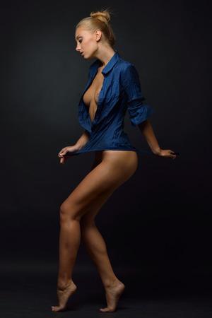 Beautiful blonde  naked woman in blue shirt posing and dancing in studio. photo