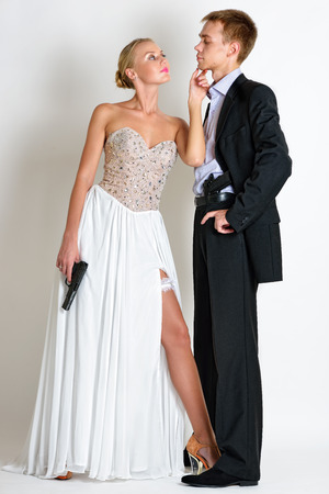 beautiful couple in evening dresses  with a guns. Photoshooting in criminal and a spy style. photo