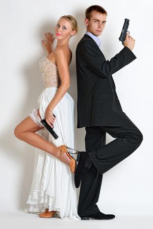 イブニング ドレス、銃を持った美しいカップル。犯罪者およびスパイ スタイルで雨音 写真素材