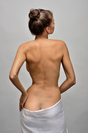 Torso portrait of the beautiful naked woman in a white towel.