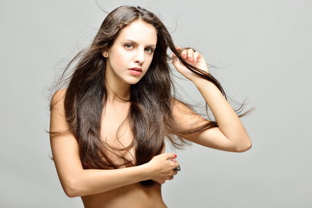 Beautiful naked woman with long hair with naked torso posing in studio.