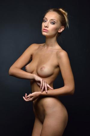 Beautiful tanned naked blonde woman posing in a dark Studio