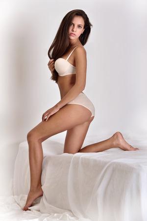 sex pose: Beautiful woman in white underwear. Studio shooting. Full length portrait. Stock Photo
