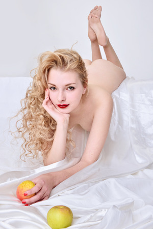 Beautiful blonde naked woman with apple lying on the white bed. Eva shape.