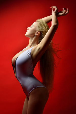 sex pose: Potrait of the beautiful blonde  woman in white lingerie in studio with red background
