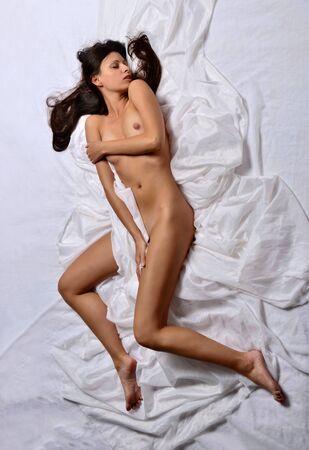 mujeres jovenes desnudas: Mujer desnuda hermosa que pone en la cama blanca. Ver desde arriba.