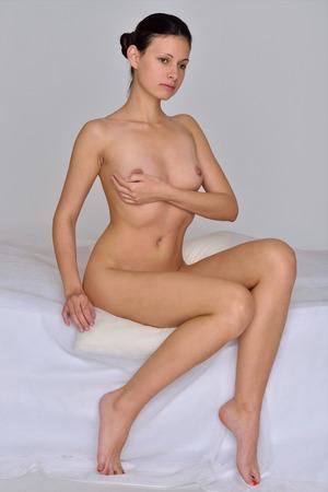 mujer desnuda sentada: Hermosa mujer sexy desnuda sentada en la cama blanca.