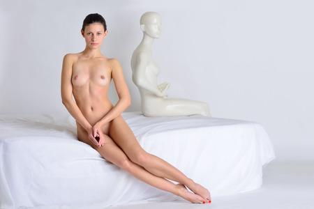 mujeres jovenes desnudas: Hermosa mujer sexy desnuda sentada en la cama blanca. El, maniquí sentado en la misma cama.